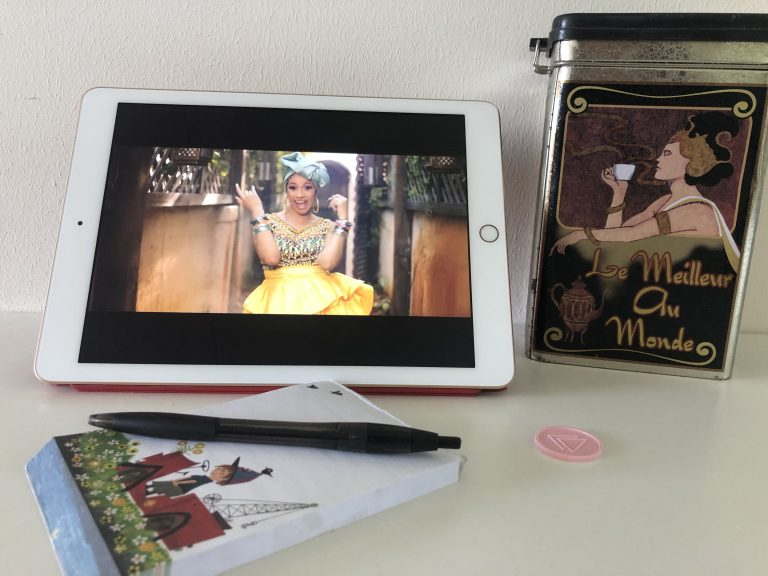 Een iPad met een still uit een clip van Cardi B., een koffieblik en een notitieboekje met pen