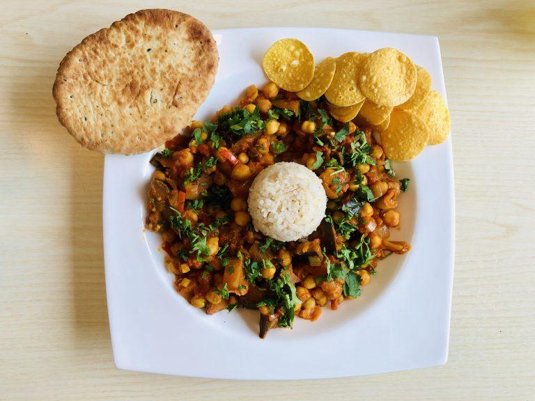 Een bord met channa masala, rijst, naan en pappadamchips