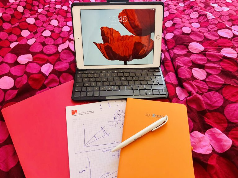 Een tablet en wat opschrijfboekjes met een pen
