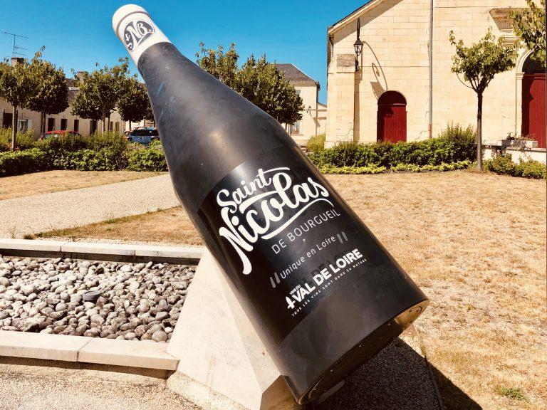 Een kunstwerk in de vorm van een grote fles wijn op een pleintje in een Frans dorpje