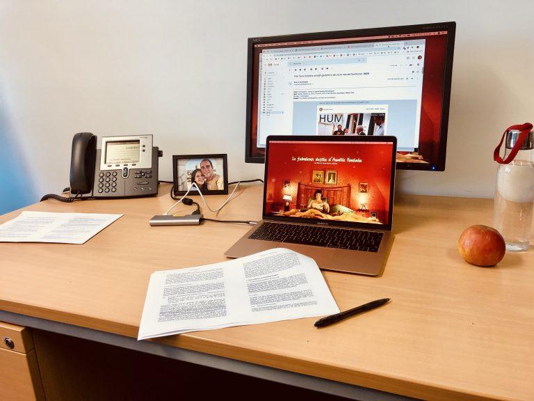 Een bureau met een computer, telefoon, pen en papier, een fles water en een appel