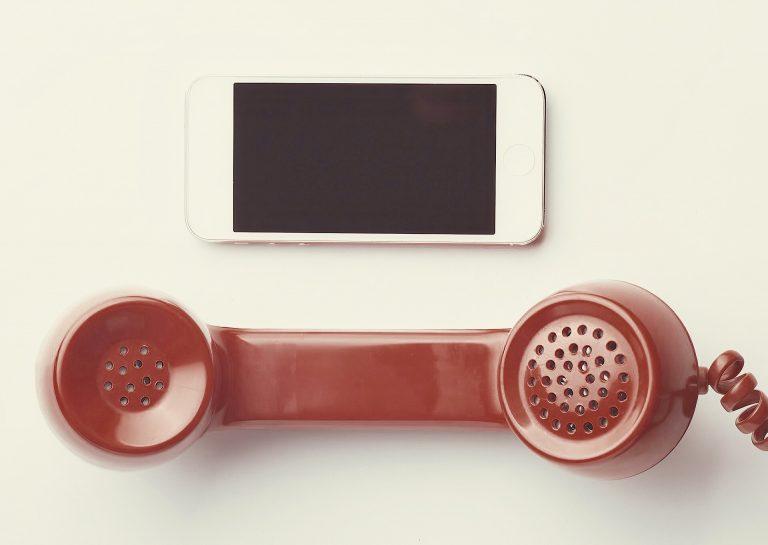 Een rode hoorn met draad van een ouderwetse telefoon en een witte iPhone