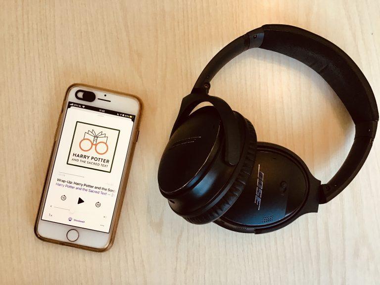 Een iPhone waarop de podcast 'Harry Potter and the Sacred Text' wordt afgespeeld naast een koptelefoon met een houten achtergrond