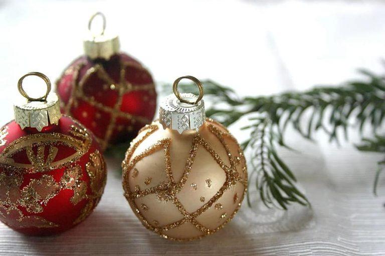 Eén goude en twee rode kerstballen en een dennentak op een tafel