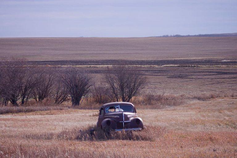 Een oud autootje zit vast in dor gras, daaromheen zie je een droog, vlak landschap