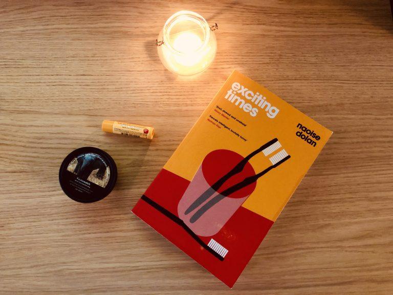 Het boek 'Exciting Times' van Naoise Dolan met een kaarsje en wat andere spulletjes op een houten ondergrond