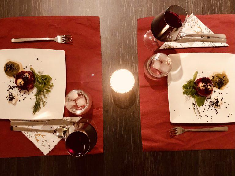 Een gedekte tafel met twee borden eten, twee glazen rode wijn en een kaarsje