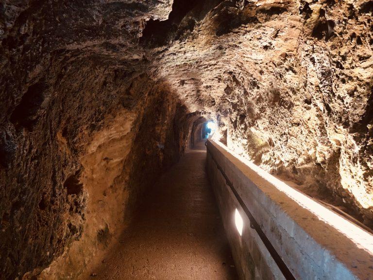 Een tunnel in een grot met licht aan het einde